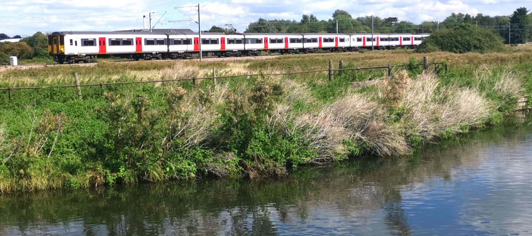 A train running alongside the New River Path near Hertford East