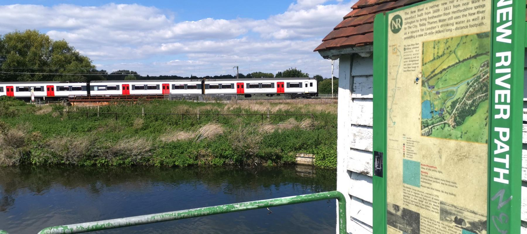 A train to London running alongside the New River Path near Hertford East