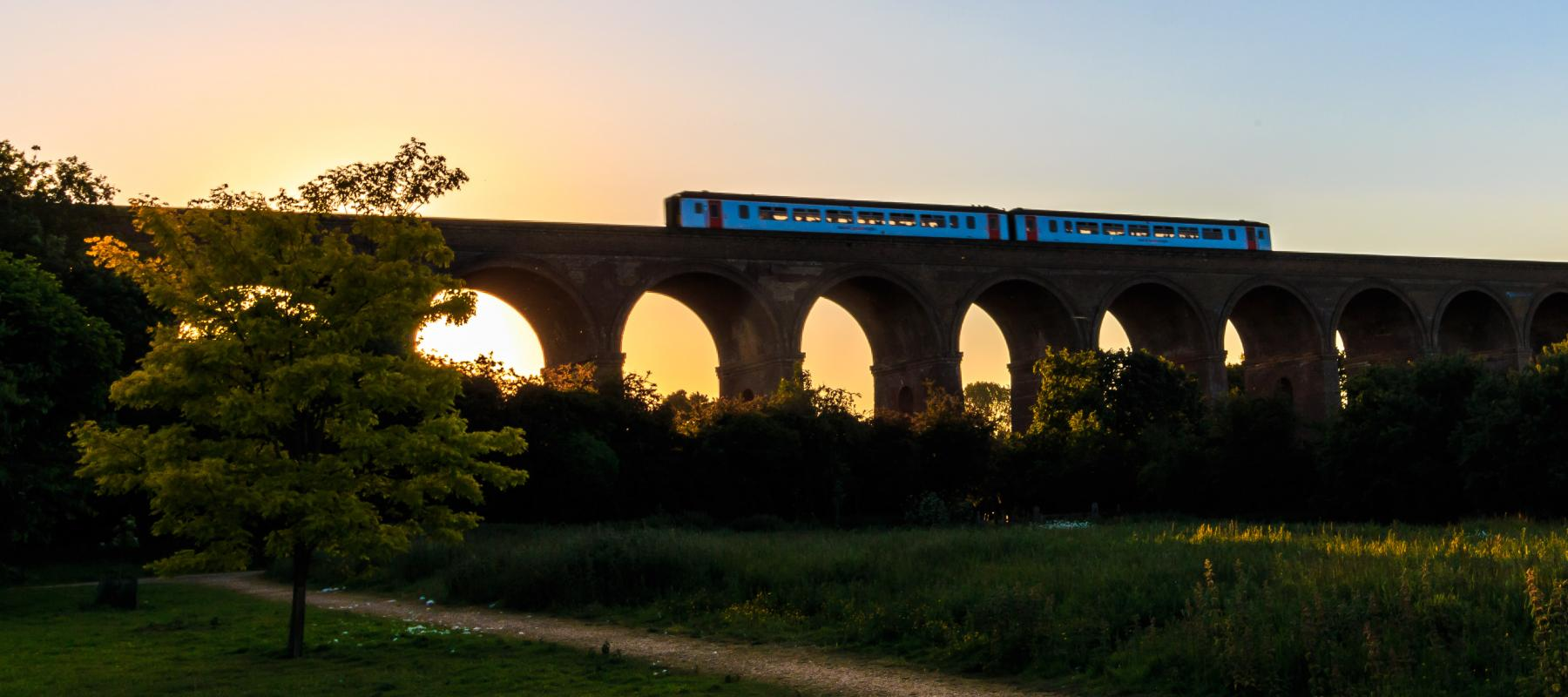 Evening train travelling across the Chappel Viaduct along the Gainsborough Line. East UK