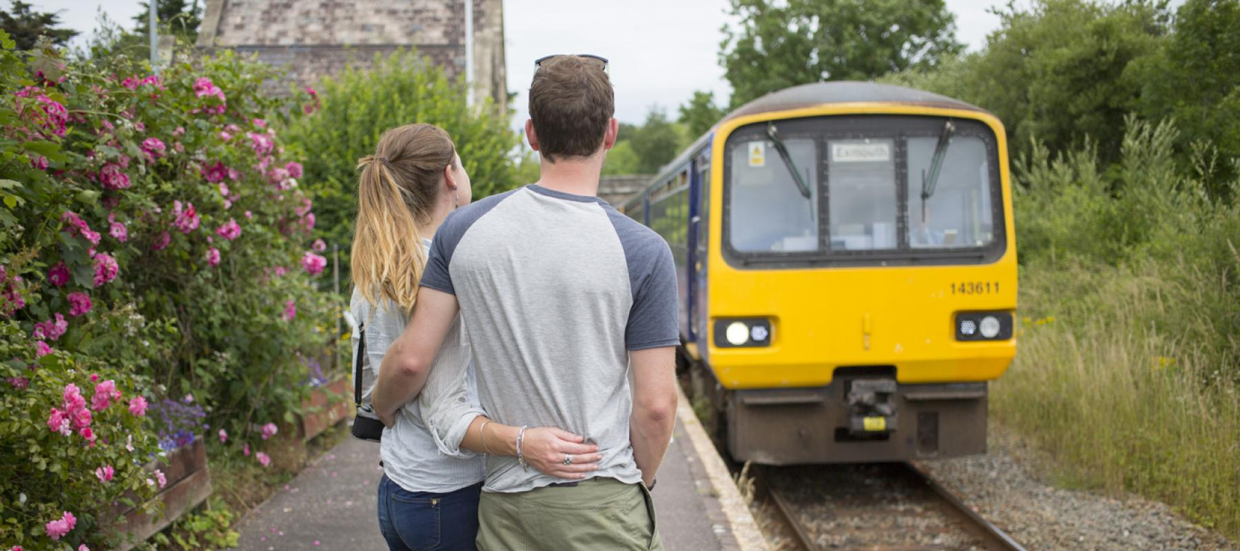 A couple wait on the platform to get on to the train on the Tarka Line