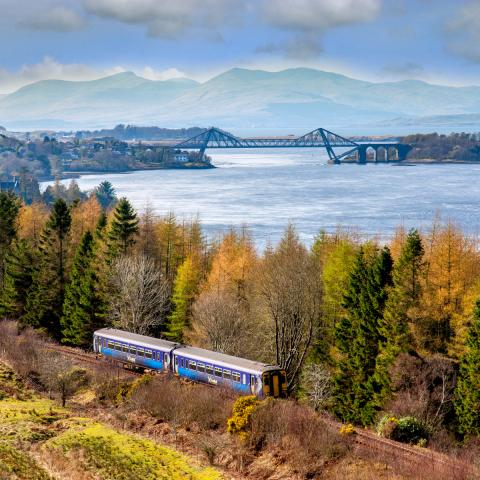 ScotRail Train travelling along the West Highland Line with Connel Bridge in the background.