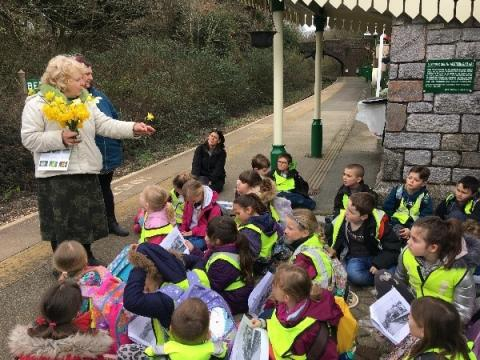 Children from Bere Alston Primary School learn about the history of daffodils at Bere Ferrers station