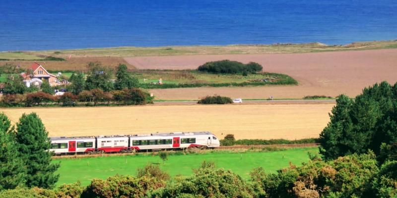 Train travelling along the coast passing West Runton on the Bittern Line
