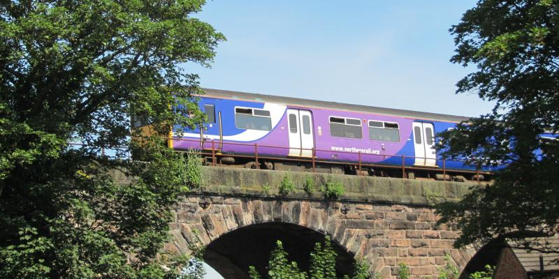 Train travelling on viaduct over Hunts Lock along the Mid Cheshire Line. North West UK.