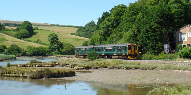 Train running alongside the estuary on the Looe Valley Line