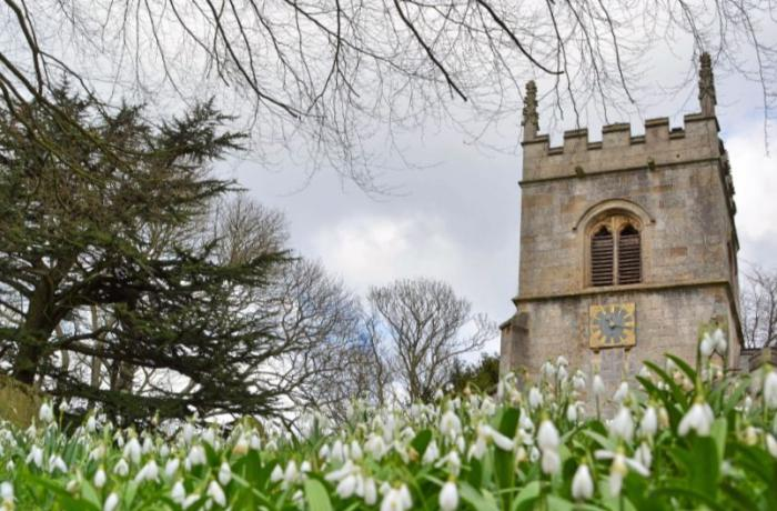 Traditional English church with snowdrops