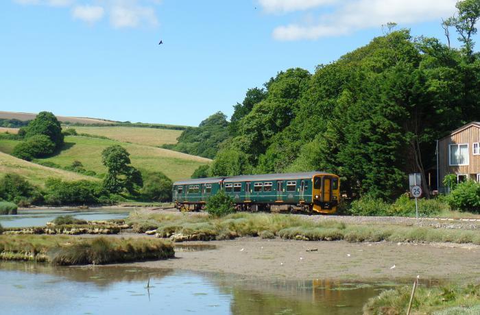Train running alongside the estuary on the Looe Valley Line